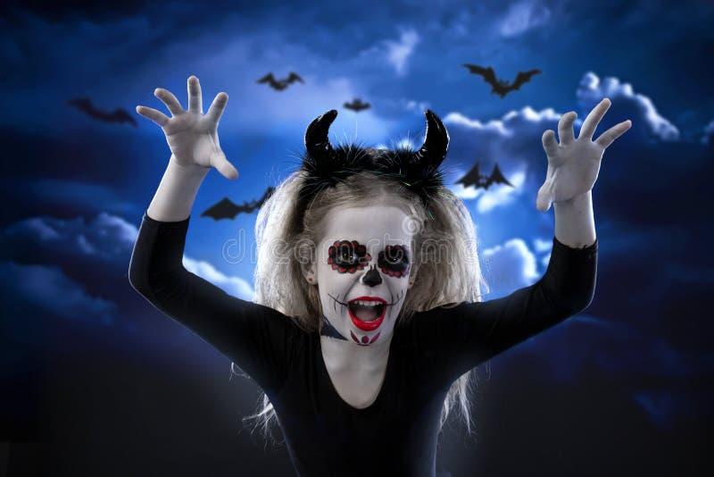 万圣夜,假日,化妆舞会概念-年轻矮小的美丽的女孩画象有头骨构成的在天空夜背景 H 库存图片