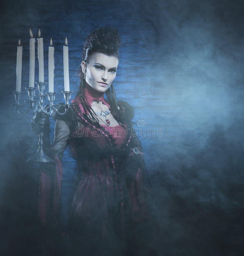 万圣夜:举蜡烛的一个小姐吸血鬼 免版税库存照片