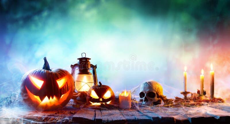 万圣夜-灯笼和南瓜在木表上 免版税图库摄影