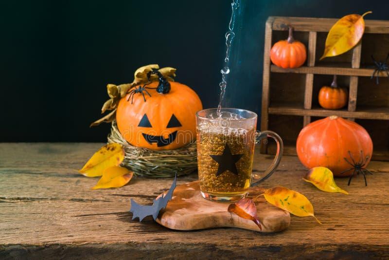 万圣节与茶的假日概念在木桌上的和南瓜装饰 免版税图库摄影