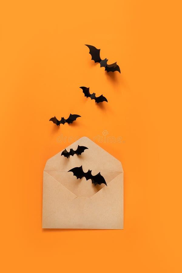 万圣节假日结构的黑棒飞行在工艺在橙色背景的纸信封外面 免版税库存图片