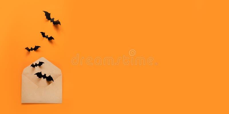 万圣节假日结构的黑棒飞行在工艺纸信封外面 免版税库存照片