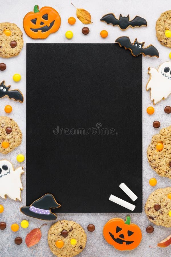 万圣节南瓜、鬼魂曲奇饼和糖果在黑板附近 库存照片