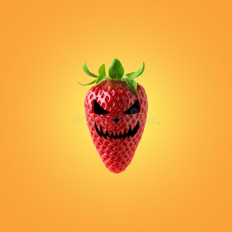 万圣节在明亮的背景的成熟草莓面对 万圣节最小的概念 库存照片