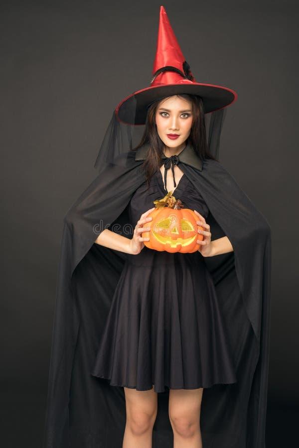 万圣节女巫画像,美丽的亚洲女人拿着南瓜雕 免版税库存照片