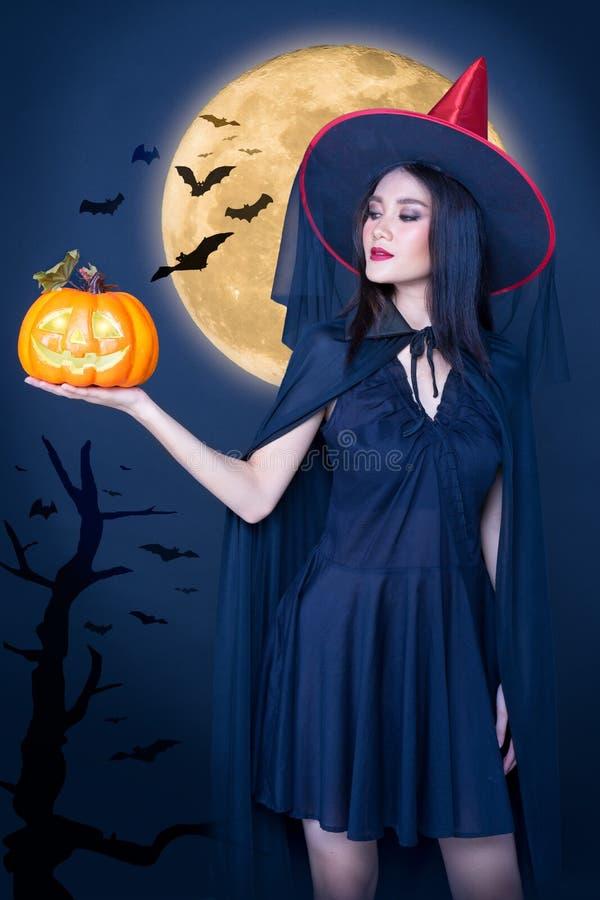 万圣节女巫画像,美丽的亚洲少女手拿月亮背景上的南瓜雕 库存照片