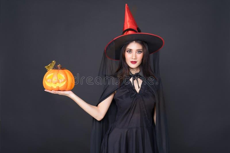 万圣节女巫画像,美丽的亚洲年轻女子手拿黑色背景上的南瓜雕 免版税库存照片