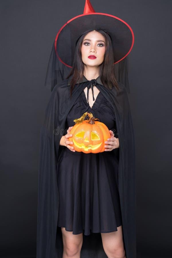 万圣节女巫画像,美丽的亚洲年轻女子手拿黑色背景上的南瓜雕 免版税库存图片