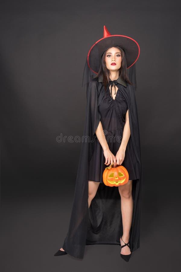 万圣节女巫画像,美丽的亚洲年轻女子手拿黑色背景上的南瓜雕 库存照片