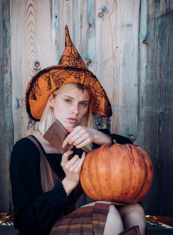 万圣节妇女 有吸引力的巫婆藏品南瓜和刀子'把戏或款待的' 在万圣节服装的妇女选矿 库存图片