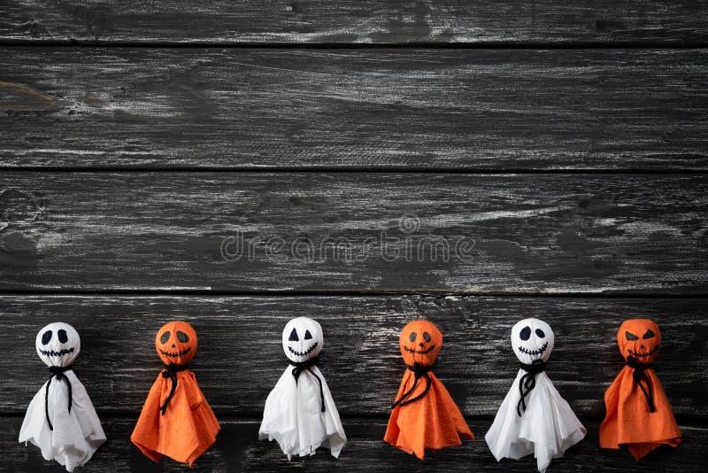 万圣节工艺,白色和橙色纸鬼魂顶视图在黑白木背景的 免版税库存图片