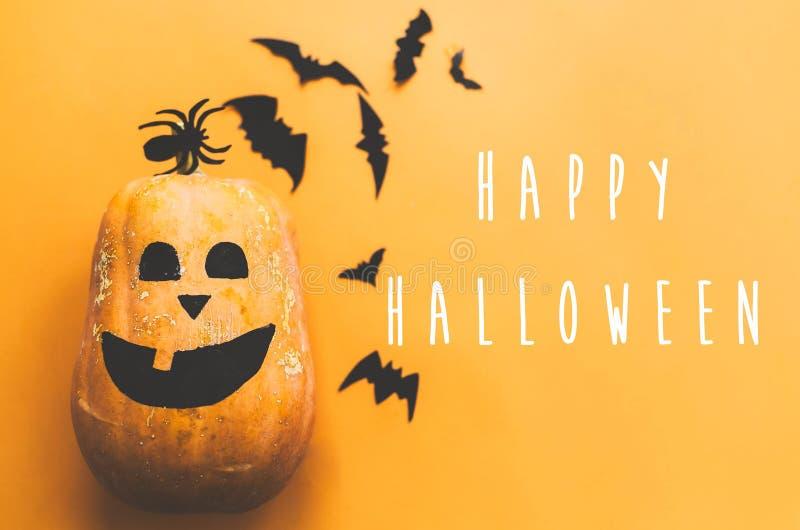 万圣节快乐短信,贺卡 有脸和黑蝙蝠的南瓜,幽灵,黄色背景上的蜘蛛纸装饰 平 库存照片