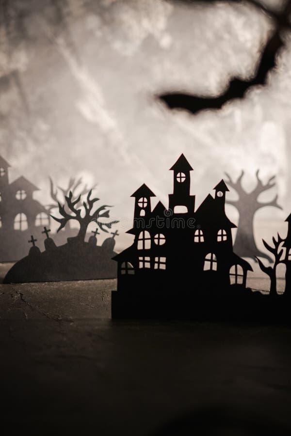 万圣节晚上背景 纸艺术 被放弃的村庄在一个黑暗的有薄雾的森林里 免版税库存图片