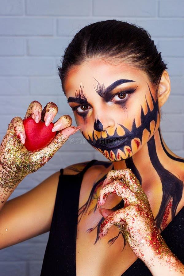 万圣节有垫铁和女孩头骨构成面孔的恶魔行家 男人和妇女做心脏手 在爱的夫妇在红色背景 免版税库存图片
