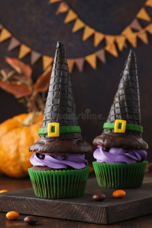 万圣节有薄酥饼巫婆帽子和糖果的杯形蛋糕妖怪 库存照片