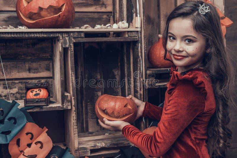 万圣节服装的逗人喜爱的女孩用被雕刻的南瓜 免版税库存照片