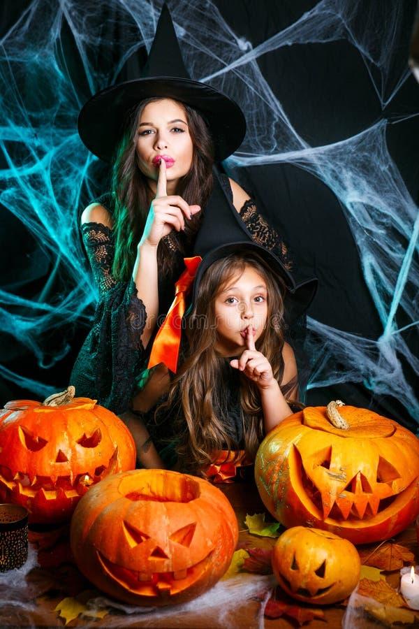 万圣节概念-快乐的巫婆服装的庆祝万圣节的母亲和她的女儿做沈默姿态 免版税库存照片