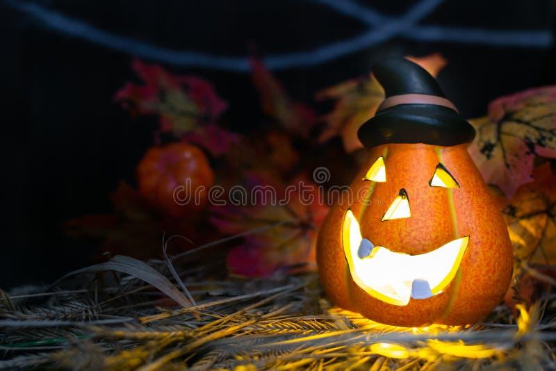 万圣节的标志 — 在蛛网背景的草草上,用一顶尖黑帽子照亮了杰克·奥兰特南瓜的头 免版税库存图片