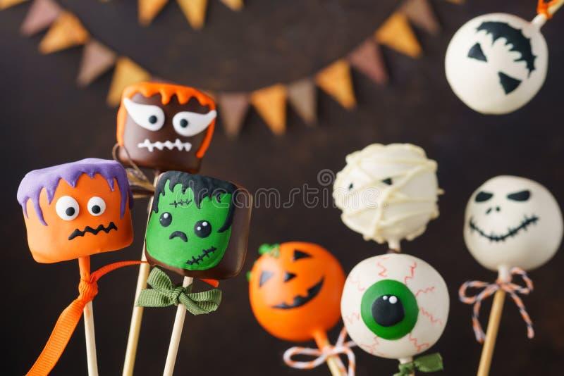 万圣节蛋糕流行音乐和蛋白软糖与滑稽的妖怪面孔 免版税库存照片