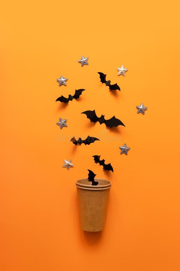 万圣节黑棒的假日概念飞行在橙色背景的纸杯外面 免版税库存照片