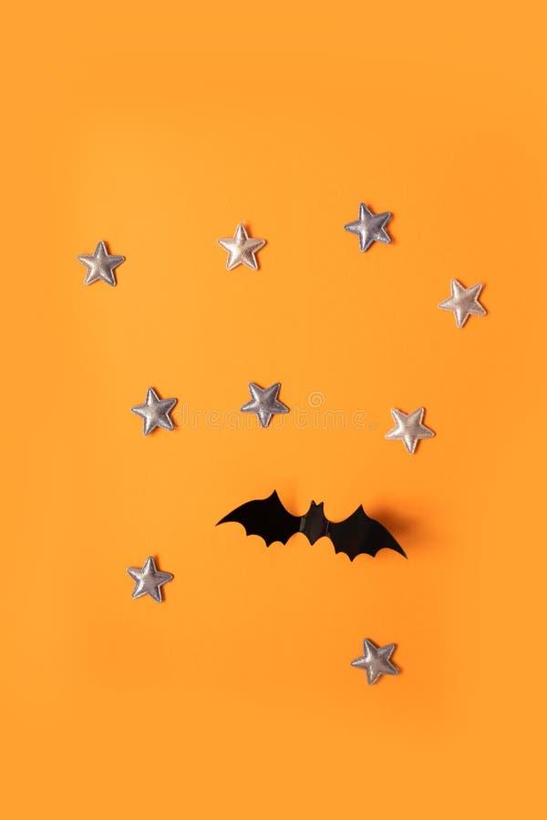 万圣节黑纸棒飞行和在橙色背景,顶视图的金星的假日概念 库存照片