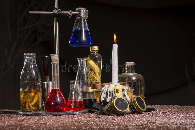 万圣节 中世纪方士` s桌 有多彩多姿的液体的烧瓶 免版税库存照片