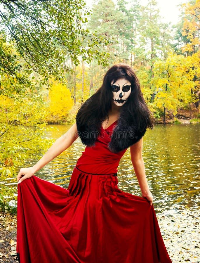 万圣节 有万圣夜头骨构成的深色的妇女在红色d 免版税库存照片
