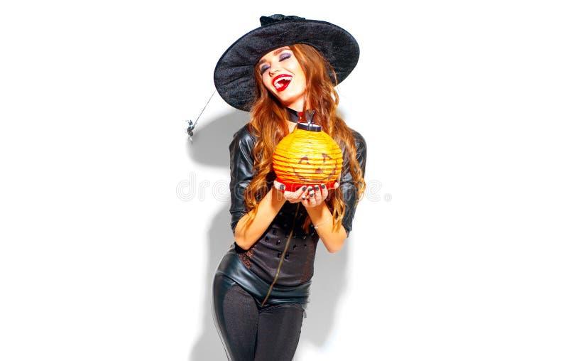 万圣节 有明亮的假日构成的性感的巫婆 摆在有南瓜灯笼的巫婆服装的美丽的少妇 免版税库存照片