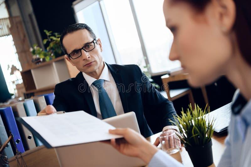 丈夫和妻子签署离婚解决 审阅离婚签署的纸的夫妇 库存图片
