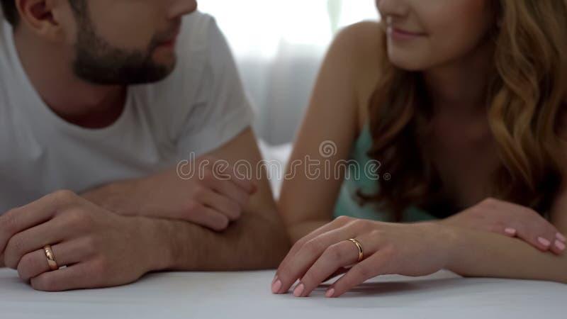 丈夫和妻子结合说谎在床上,看彼此,爱恋的年轻家庭 免版税图库摄影