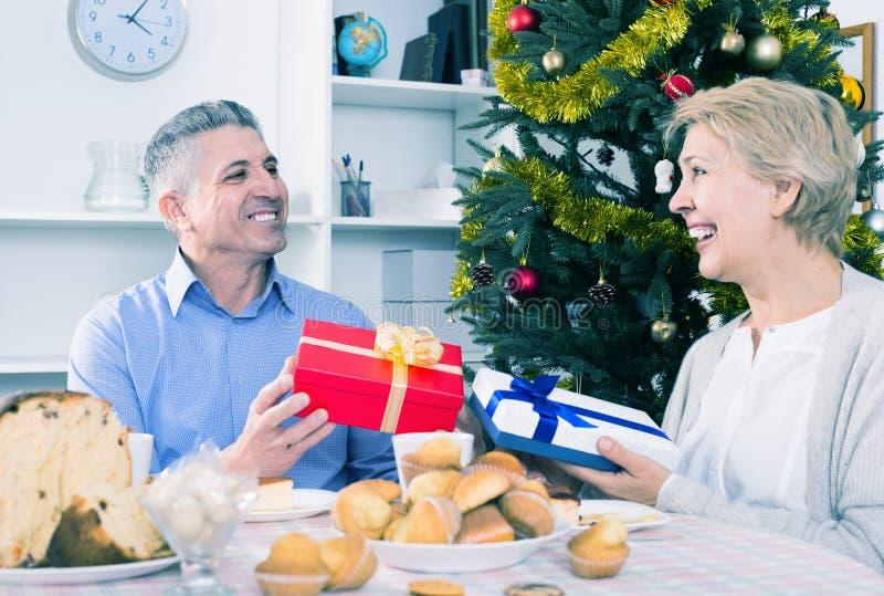 丈夫和妻子为圣诞节和新的Ye交换节日礼物 库存图片
