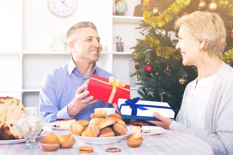 丈夫和妻子为圣诞节和新的Ye交换节日礼物 免版税库存图片