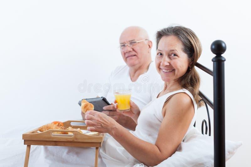 丈夫和妻子在床上的吃早餐 免版税库存图片