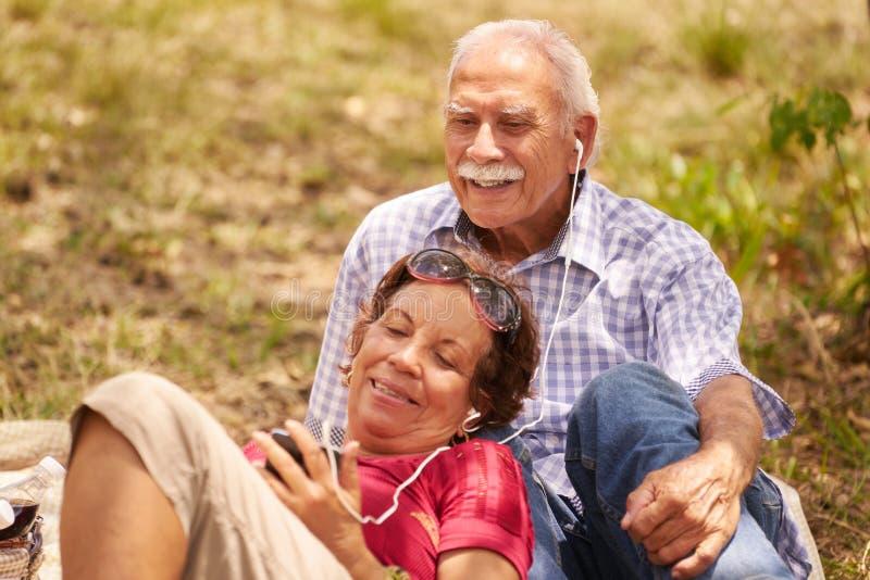 丈夫和妻子老人妇女听的音乐 免版税库存图片