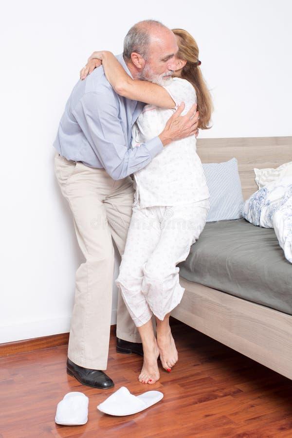 丈夫帮助妻子下床 免版税图库摄影
