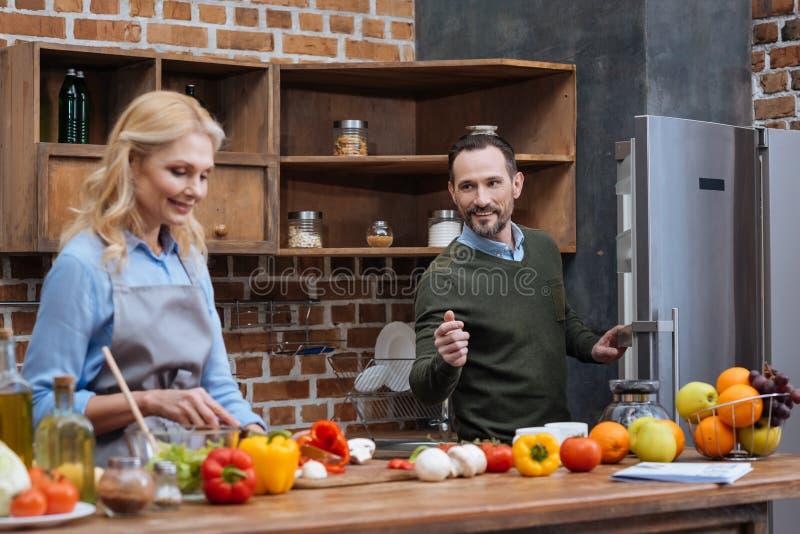 丈夫谈话与妻子,当她烹调时 图库摄影