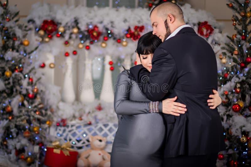 丈夫轻轻地拥抱他怀孕的妻子在圣诞节 免版税库存照片