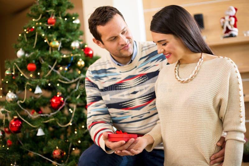 丈夫给一个礼物他圣诞节holid的可爱的妻子 库存照片