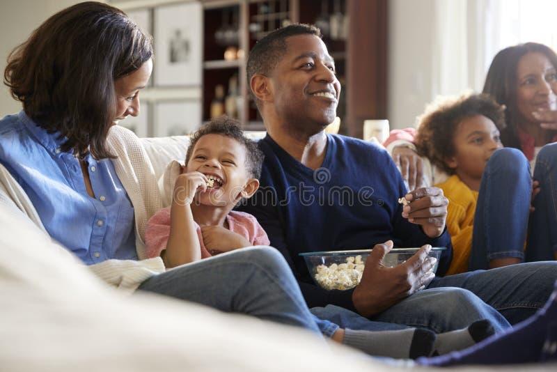 三一代坐沙发在客厅,看着电视和吃玉米花,选择聚焦的家庭家庭 免版税库存图片