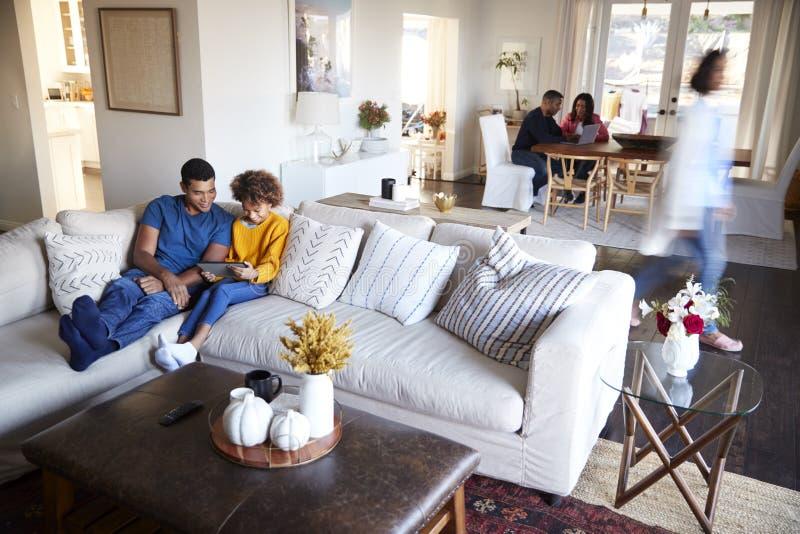 三一代花费在他们的开放学制客厅和厨房吃饭的客人、父亲和女儿的家庭家庭时间foregrou的 免版税库存照片