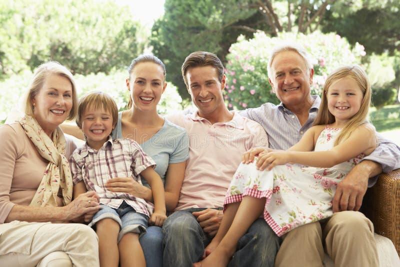 三一代家庭一起坐沙发 库存图片
