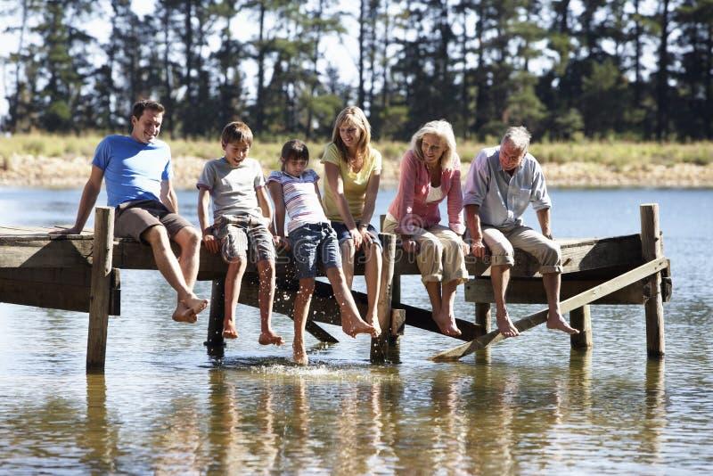 三一代家庭坐看在湖的木跳船 免版税库存照片