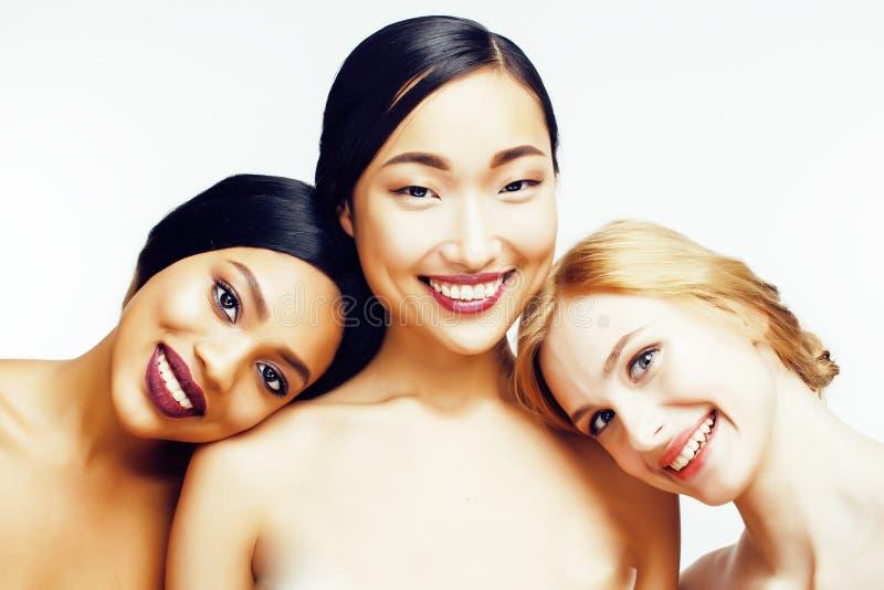三不同国家妇女:亚洲人,非裔美国人,在白色背景愉快微笑一起隔绝的白种人 免版税库存图片