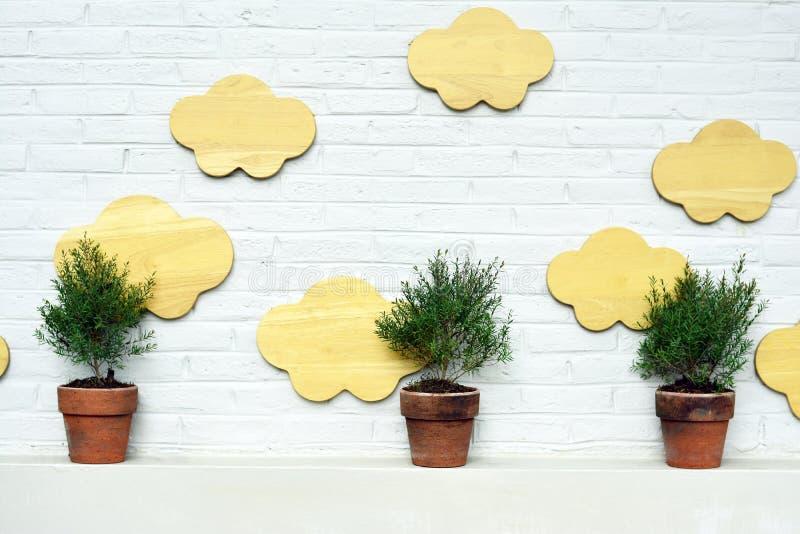 三与云彩木头的花盆在现代砖墙后面 免版税库存图片
