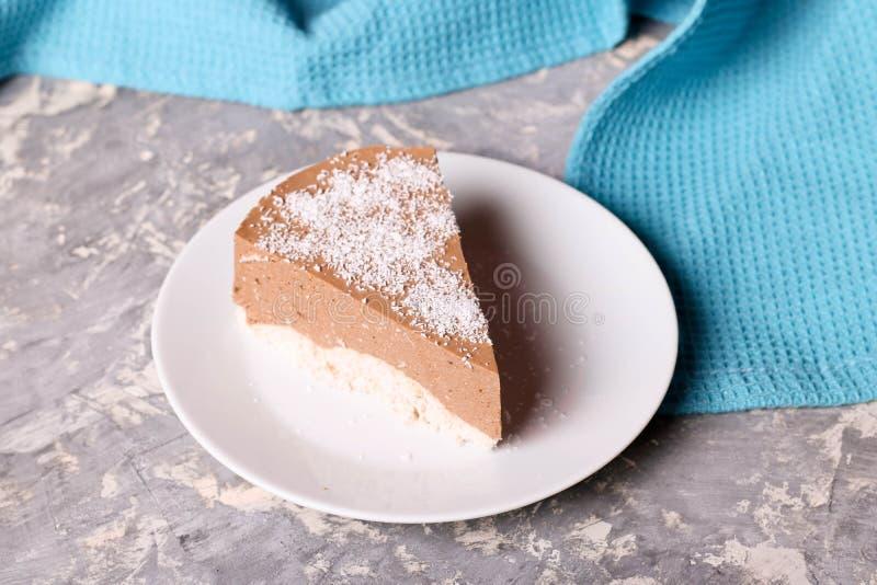 三与椰树切片的巧克力沫丝淋蛋糕在一块小板材 库存照片