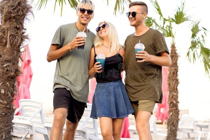 三个一个热带海滩和饮料鸡尾酒的朋友快乐的公司基于;非常;杂志概念 免版税图库摄影