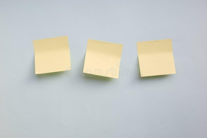 三个与拷贝空间的黄色纸贴纸笔记在蓝色背景 库存图片
