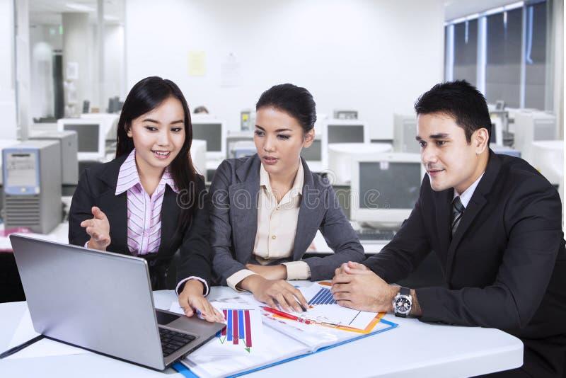 三个亚洲人与膝上型计算机的企业队在办公室 免版税库存照片