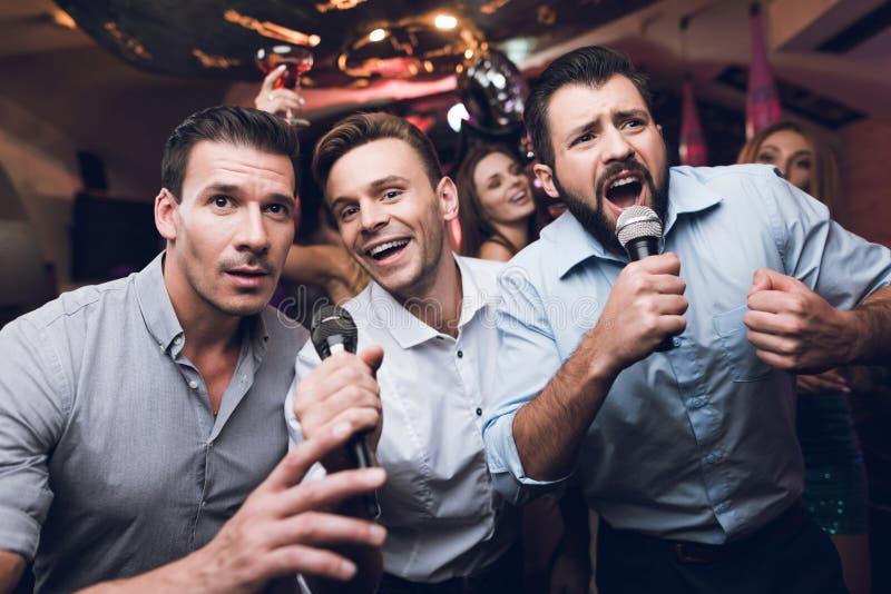 三个年轻人的夜场人生_三个人唱歌在卡拉ok演唱俱乐部 青年人获得乐趣在夜总会 他们是非常