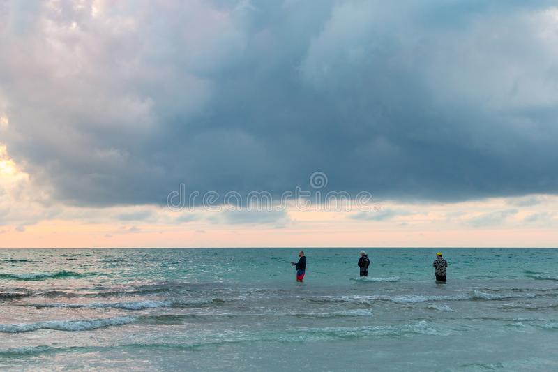 三个人钓鱼在海洋 免版税库存图片